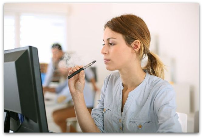 Girl smoking with electronic cigarette in office